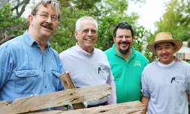 Four men participate in a neighborhood development project